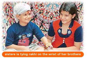 sisters is tying rakhi on the wrist of her brothers